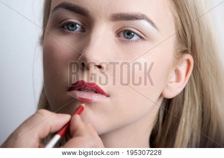 Girl Getting Red Pencil On Lips By Male Hand
