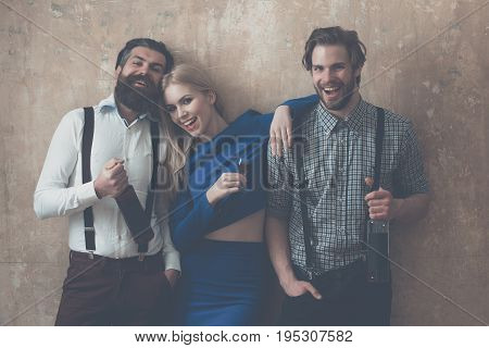 Woman holding glass of liqueur and men with wine bottles. Happy friends with alcoholic drinks on beige background. Alcohol and appetizer. Friendship and convives. Unhealthy lifestyle and bad habits