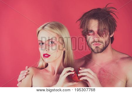 couple of woman and man with creative fashionable makeup on face hold pomegranate fruit on red background beauty and fashion allergy healthcare and vitamin vegetarian and dieting hemoglobin