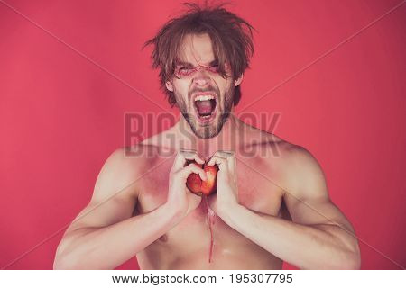 man with creative fashionable makeup on shouting face hold pomegranate fruit in hands on red background beauty and fashion allergy healthcare and vitamin vegetarian and dieting hemoglobin