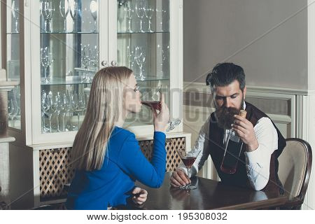Man And Woman Sharing Bottle Of Red Wine In Restaurant