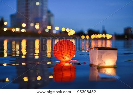 Paper Chinese lanterns floating in river with city lights reflections selective focus