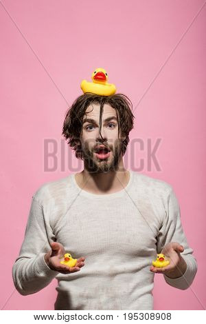 surprised man with duckling toy in bath or shower with wet hair on pink background hygiene and skincare health and wakeup