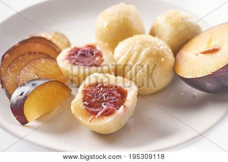 Top view of austrian popular dish called knoedel with plum jam and cinnamon on white plate