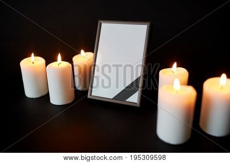 funeral and mourning concept - empty photo frame with ribbon and burning candles over black background