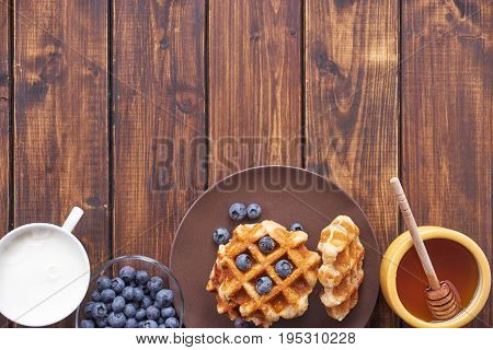 Top view of beligain waffles, cup of milk and honey making bottom border on dark woodaen background with space for text