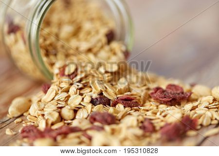 food, healthy eating and diet concept - close up of jar with granola or muesli poured on table