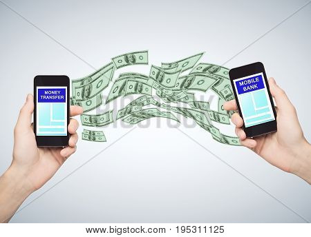 Mobile bank concept. Hands holding two cellphones with abstract dollar flow. Gray background. 3D Rendering