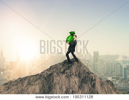 Young businessman standing on mountain top and holding heavy money bag on sky background. Wealth and winning concept