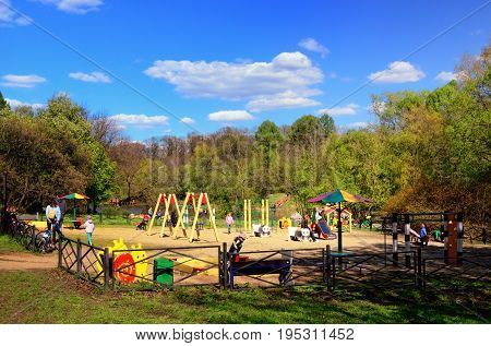 MOSCOW, RUSSIA - MAY 14, 2017: Children's Playground in a Green Park in May with Kids Playing and Parents on May 14, 2017 in Moscow, Russia