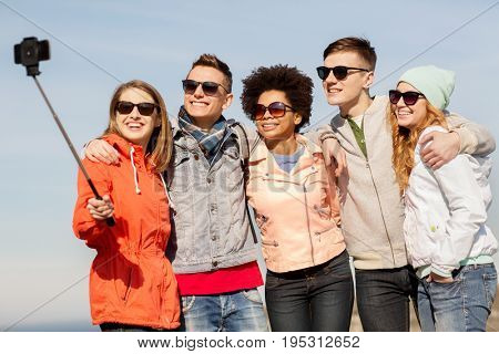 people, friendship and technology concept - group of smiling teenage friends taking picture with smartphone selfie stick outdoors