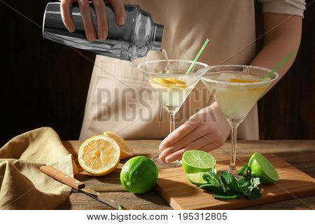 Woman making cocktail with tequila at table