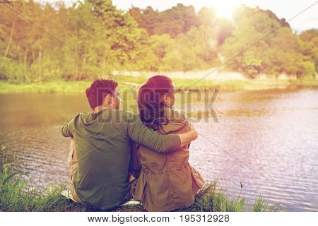 love, travel, hiking, tourism and people concept - happy couple hugging and enjoying natural view on lake or river bank
