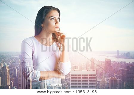 Thoughtful young woman on abstract city background. Employment concept. Double exposure