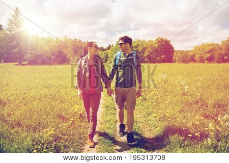 travel, hiking, backpacking, tourism and people concept - happy couple with backpacks holding hands and walking along country road outdoors