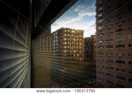 HOBOKEN NEW JERSEY - December 01 2016: Window with blind reflection and dramatic sunlight shining through among office and residential buildings at golden hour