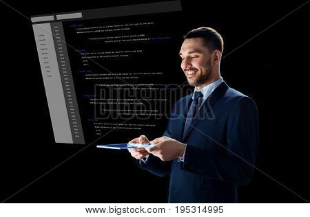 business, people and future technology concept - smiling businessman in suit working with transparent tablet pc computer and coding on virtual screen over black background