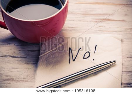 Cup of coffee and napkin with message on wooden table