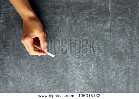 One female hand holding a piece of chalk against blank chalkboard. Copy space.