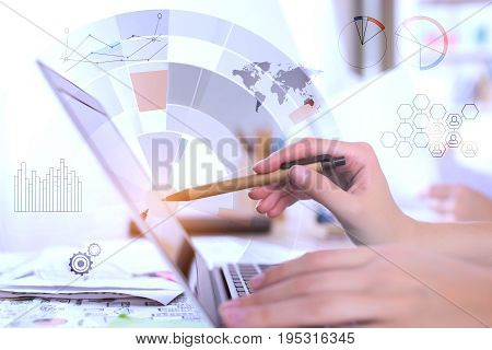 Side view of young female hands using laptop keyboard placed on desktop with items and abstract digital business hologram. Technology finance and accounting concept. Double exposure