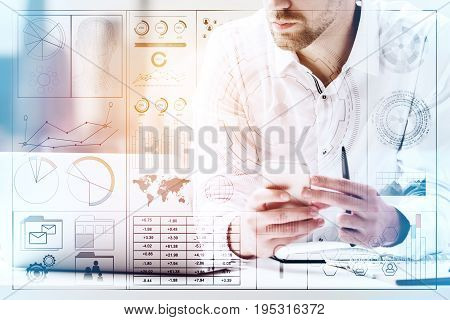 Handsome businessman at workplace using smartphone and using laptop. Toned image. Creative digital business hologram layer. Technology and communication concept. Double exposure