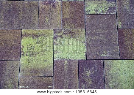 Stone texture of gray brown paving slab on the road