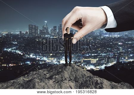 Huge businessman hand placing young businessman on mountain top. Night city background. Success and victory concept
