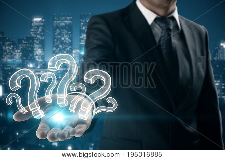 Businessman holding drawn glowing question marks on night city background. Confusion concept
