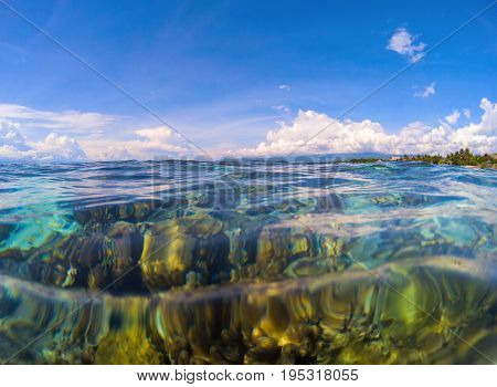 Marine landscape with transparent water and sky. Transparent seawater with coral reef under water. Double landscape with sea and sky. Clean sea water with ripples. Sunny day on tropical seashore