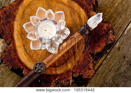 Candle Burning In Crystal Lotus Flower Holder Sitting On Cross Section Of Timber Log With Wiccan Wan