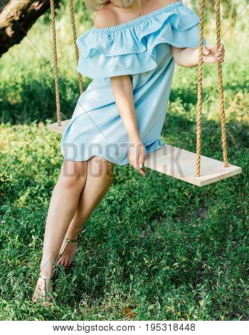 Beautiful young woman in blue dress sitting on swing under tree on summer day outdoors. Young woman having fun on swing in nature