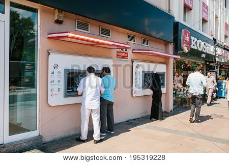 Istanbul, June 11, 2017: Local residents withdraw money from an ATM in Istanbul. Life style. Routine. Everyday life. Finance