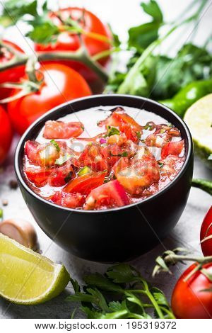 Traditional Latin American mexican salsa sauce and ingredients on black stone table. Close up.