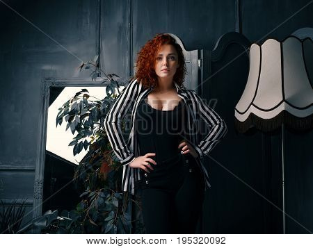 Ginger girl at home next to the mirror, lamp and homeflower