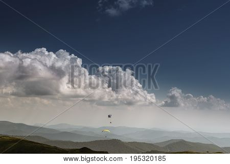 Summer view of Carpathian Mountains and Valleys, under blue sky with clouds. With pair of paragliders in sky