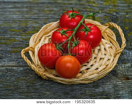 Bunch of fresh tomatoes and tomato juice in glass on wooden table
