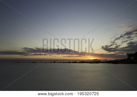 Sunset over Ocean with Breakwater and rowboat in Gotland Sweden.