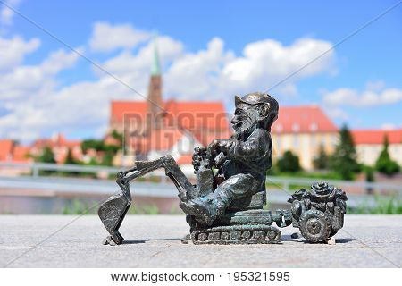 WROCLAW POLAND - JUNE 2017: The symbol of Wroclaw. A small gnome sculpture in the background of the panorama of Wroclaw.