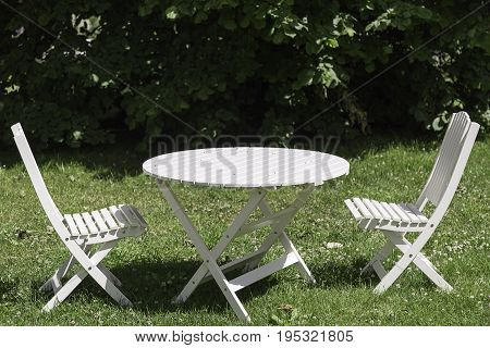 White Garden Chairs and Table with green grass.