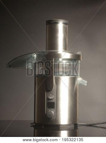 Metallic professional juicer on black background .