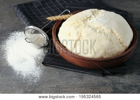 Raw dough in bowl and sieve with flour on grey table