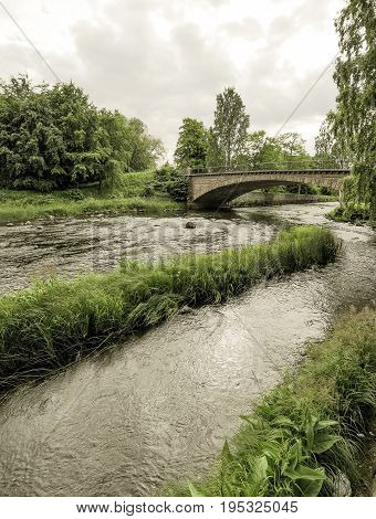Stone Bridge over Gavle River with a cloudy sky.