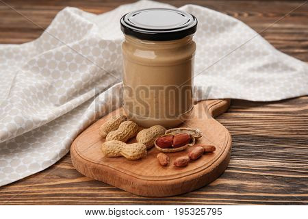 Jar with creamy peanut butter on table