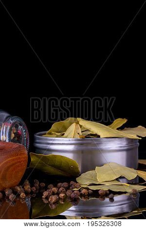 Spices and herbs, bay leaf, black peppercorn on black background with reflection, copy space