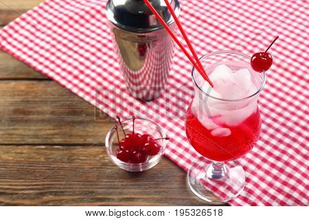 Delicious cocktail with tequila and maraschino cherry on table