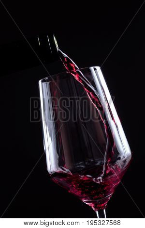 Red wine pouring in wineglass from a bottle on black background. Wine list design menu with copyspace. Alcohol beverage card backdrop.