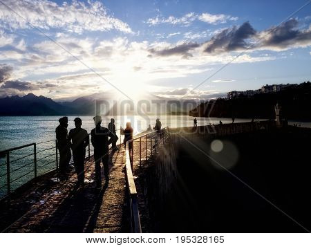 silhouetted  people walking on street over sunset sky with sunbeam