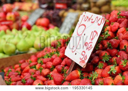 Mahane Yehuda Market in Jerusalem. Close up strawberries for sale written information: Strawberries 990 shekels