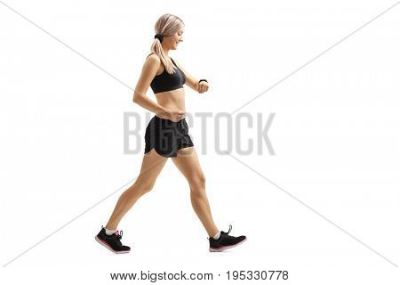 Full length profile shot of a woman walking and checking her sports watch isolated on white background