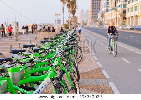 TEL AVIV ISRAEL- APRIL 2017: Parked bicycles in center of Tel Aviv.Tel-O-Fun is a bicycle sharing service which provided by the city including 125 active stations. Blurred view of the embankment of Tel Aviv and bike roads.